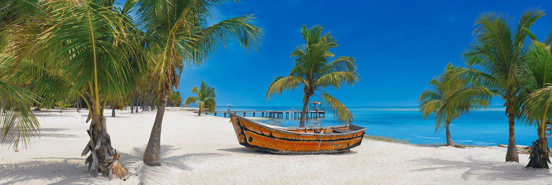 Old wooden boat sitting on a white sand beach full of palm trees with a jetty and the ocean in the background