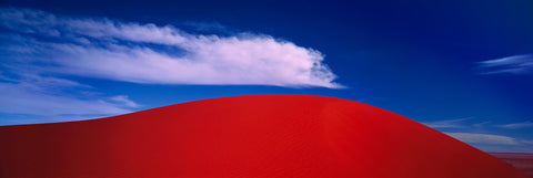 Red windswept sand dunes under cloudy blue skies in the Simpson Desert Australia