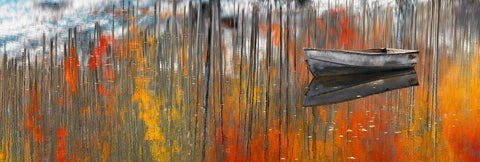 Old metal row boat floating on a lake in Aspen Colorado with the Autumn forest reflecting in the water