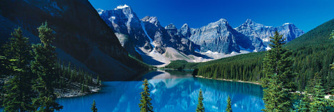 Turquoise water of Lake Moraine Canada surrounded by a forest of pine trees and rocky mountains