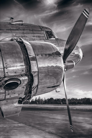 Black and white close up side view of the engine and cockpit of a DC-3 airplane on a runway in Aurora Oregon