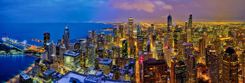 Rooftop view of downtown Chicago and Lake Michigan shoreline lit up at night