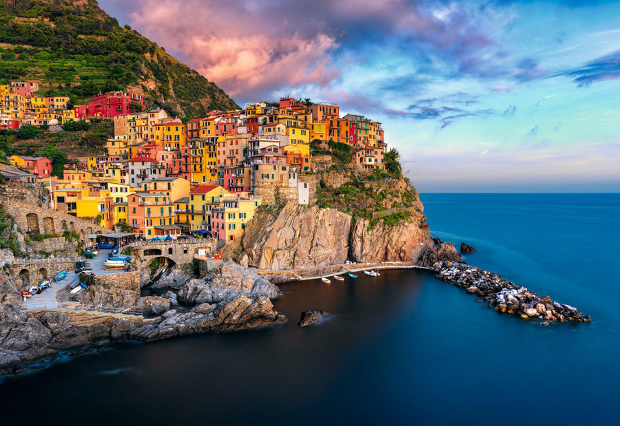 Colorful painted buildings of Manarola Italy built on a cliff overlooking the ocean at sunset