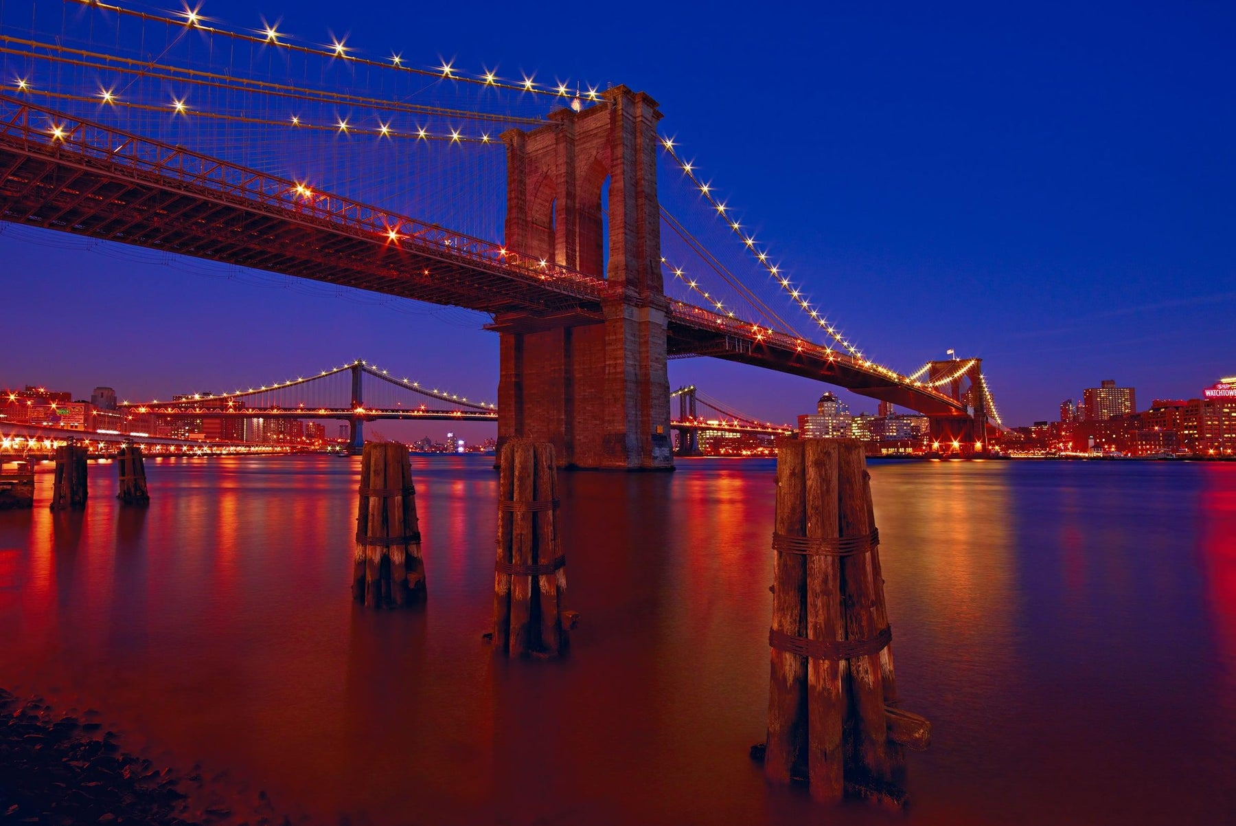 Brooklyn Bridge lit up at night from the waters edge with the Manhattan Bridge and New York City in the background