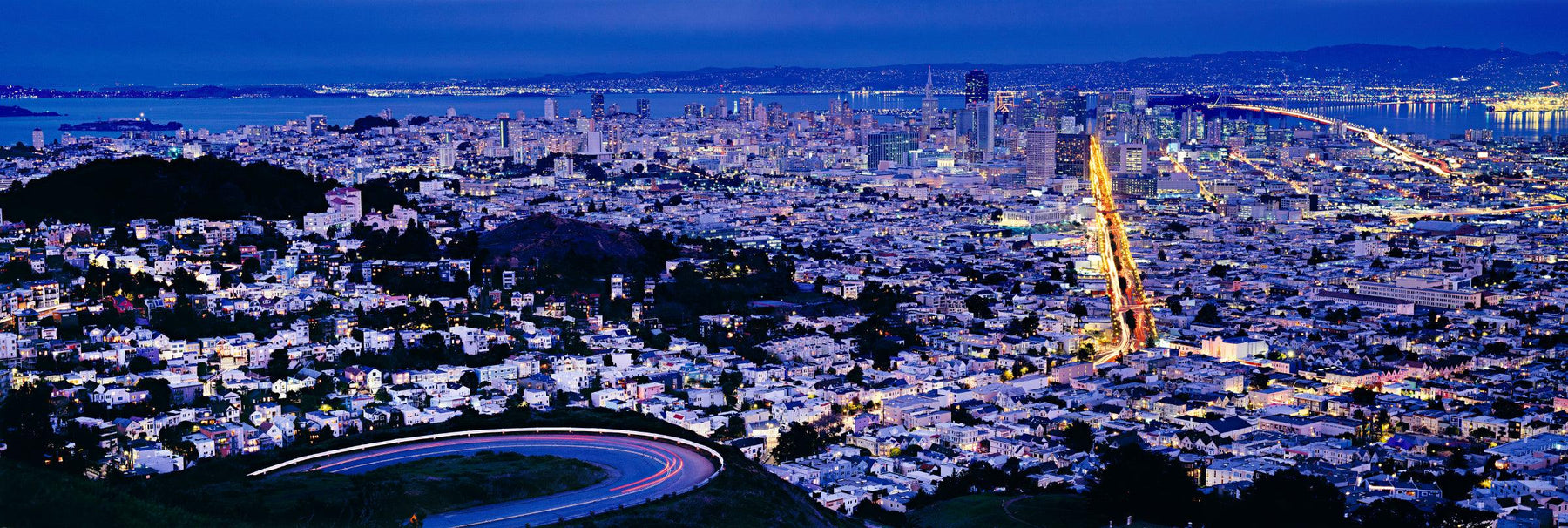 View from the hillside looking down at the lit up traffic and city of San Francisco at night