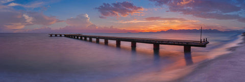 Old concrete jetty stretching out over the ocean and Cilento Coast Italy at sunset