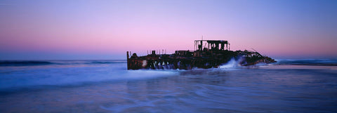 Waves crashing on the Maheno ship wreck on Fraser Island Australia at twilight