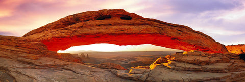 Stone arch glowing red from the sun rising over the stone peaks and and valley of Canyonlands National Park Utah