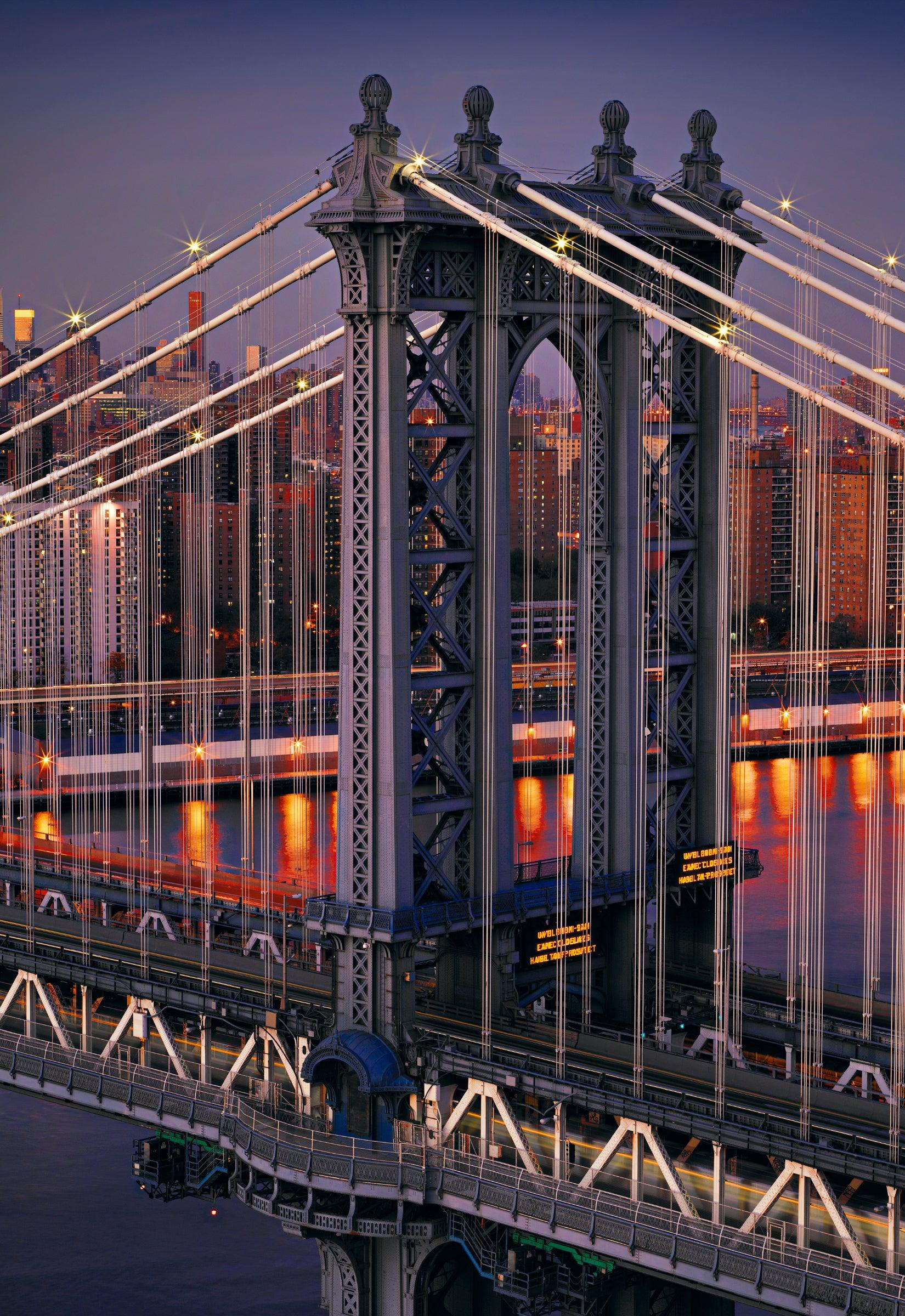 Section of the Manhattan Bridge lit up at night overlooking the glow of New York City in the distance