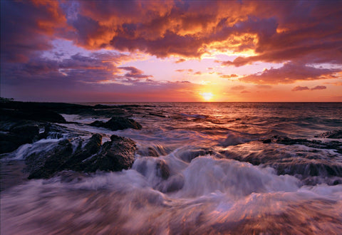 Waves crashing on the rock and sand beach of Mauna Lani Hawaii as the sun sets through a cloud filled sky