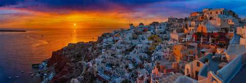 White and orange buildings along the cliffs of Santorini Greece with the sun setting over the ocean behind