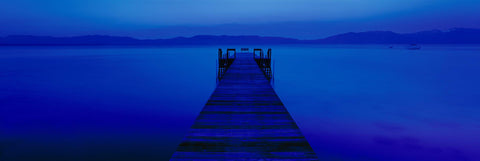 Wooden jetty stretching over Lake Tahoe under the blue monotone light of the moon