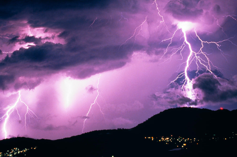 Lightning in the cloudy purple sky over the hills of the Copperlode Dam in Australia at night