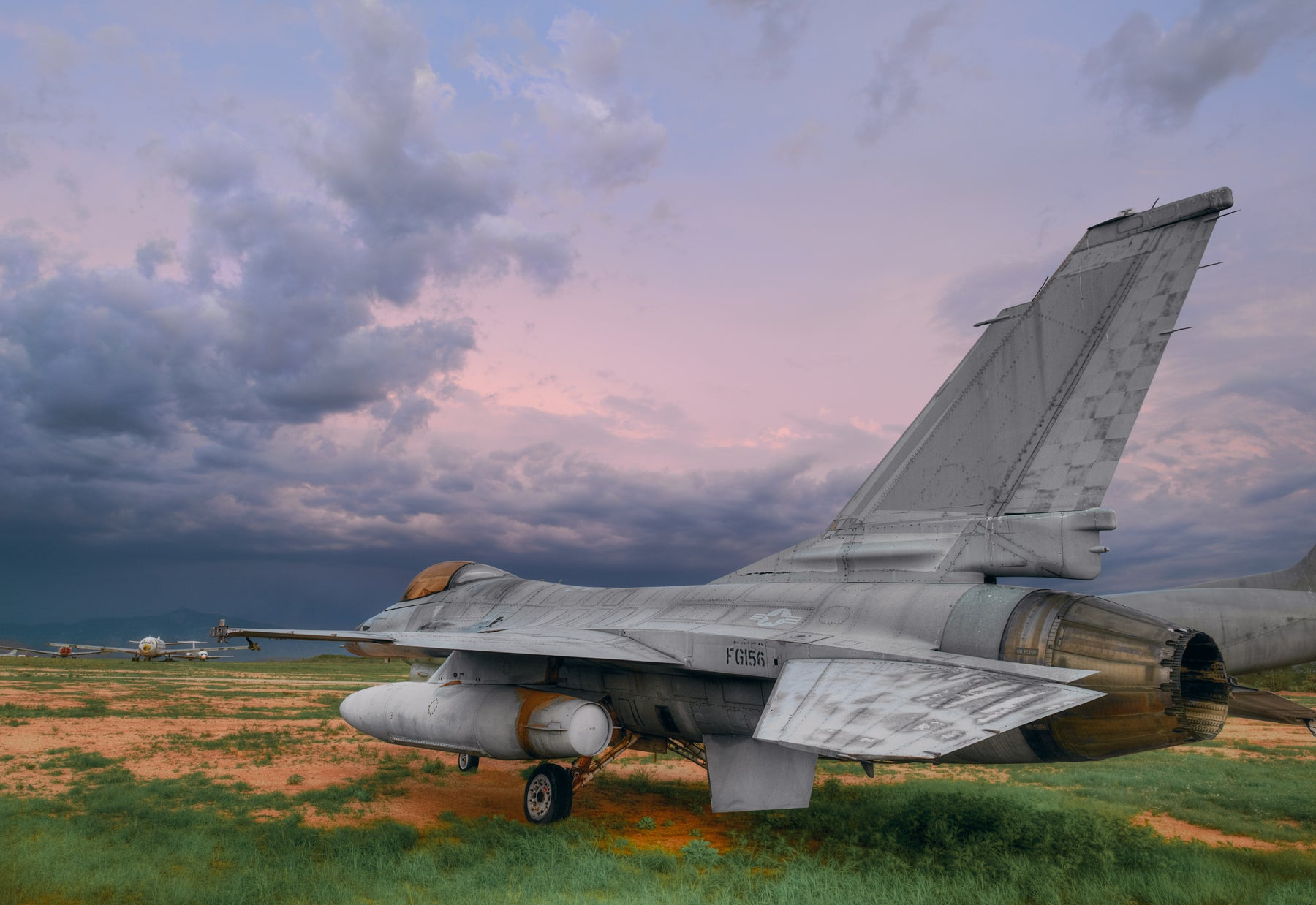 Old F-16 fighter jet sitting on a grass and dirt field in Tucson Arizona with a storm on the horizon