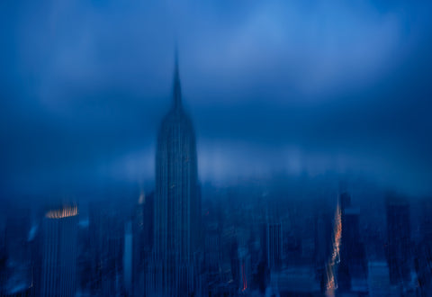 Blurred rooftop view of the Empire State Building and New York City on a stormy day