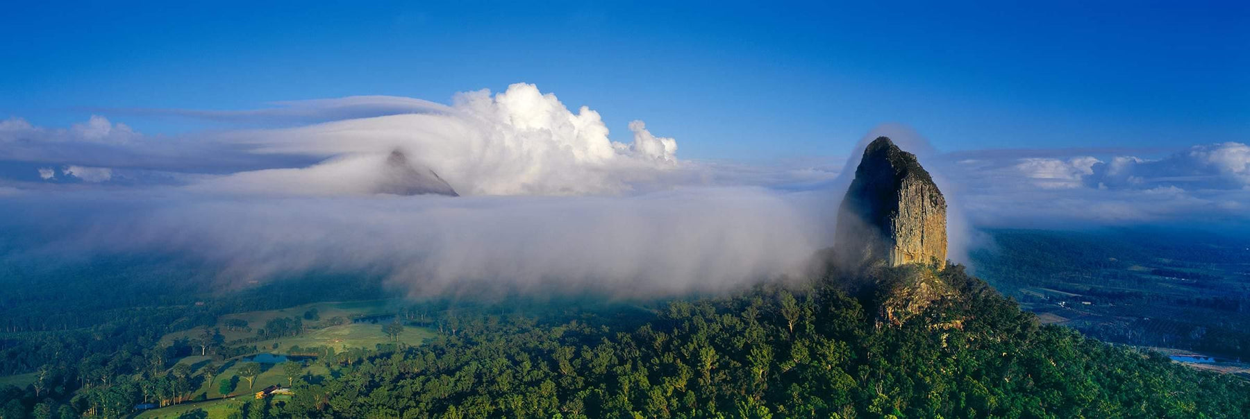 Mountain peaks covered by rolling clouds in the tree covered plains of Glass House Mountains National Park Australia