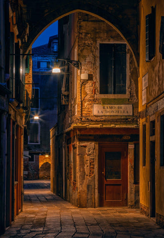 Old stone building facades on Venice Italy lit by street lights at night