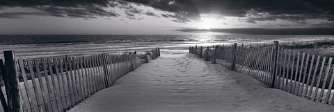 Black and white sand pathway with picket fences leading to a beach in Newport Rhode Island during sunrise