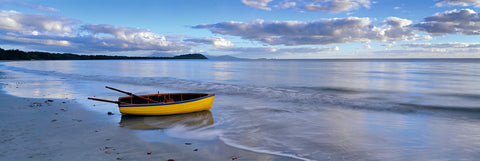 Yellow rowboat washed a shore on the wet sand beach in Port Douglas Australia