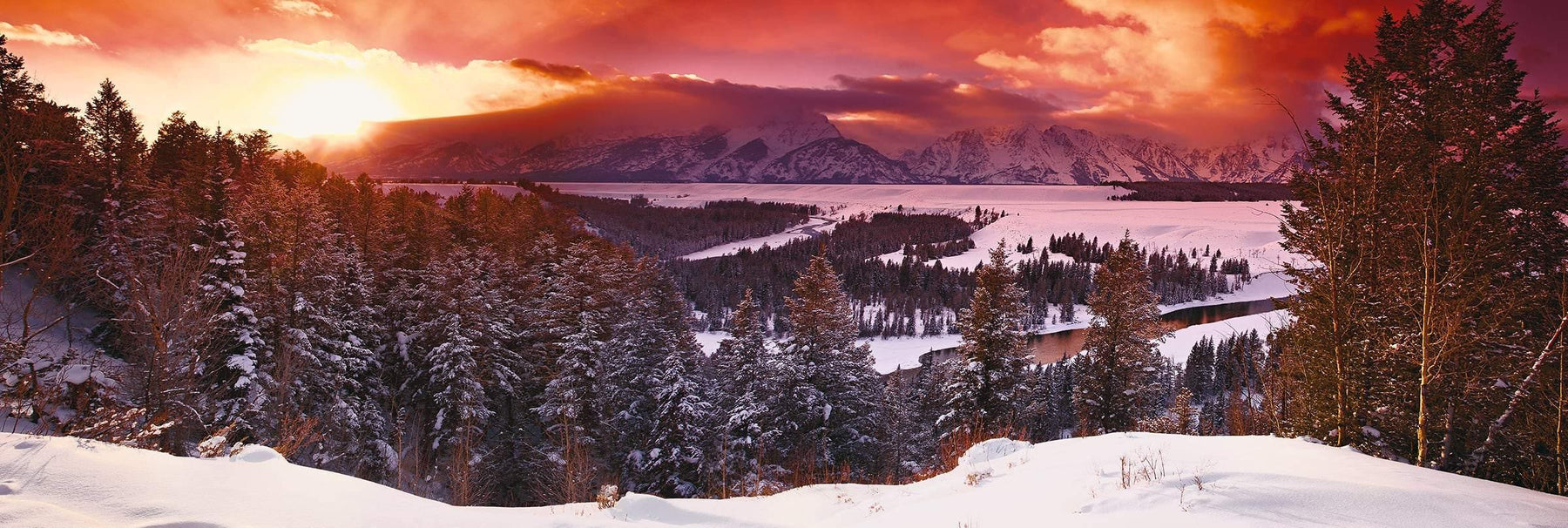 Sun shining through the clouds as it sets on the snow covered valley and forest of Grand Tetons National Park Wyoming