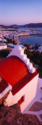 Red and white rooftop of a church overlooking the city of Mykonos Greece and its bay full of boats