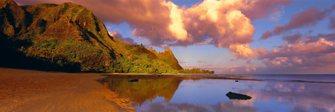 Water filled tide pools reflecting the clouds and cliffs along the shoreline of the Na Pali Coast Hawaii
