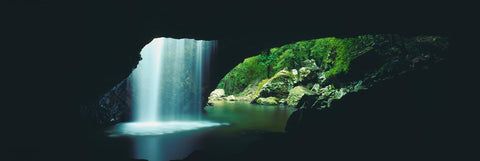 View from the inside of a cave looking out with water falling from a hole in the ceiling in Lamington national Park Australia