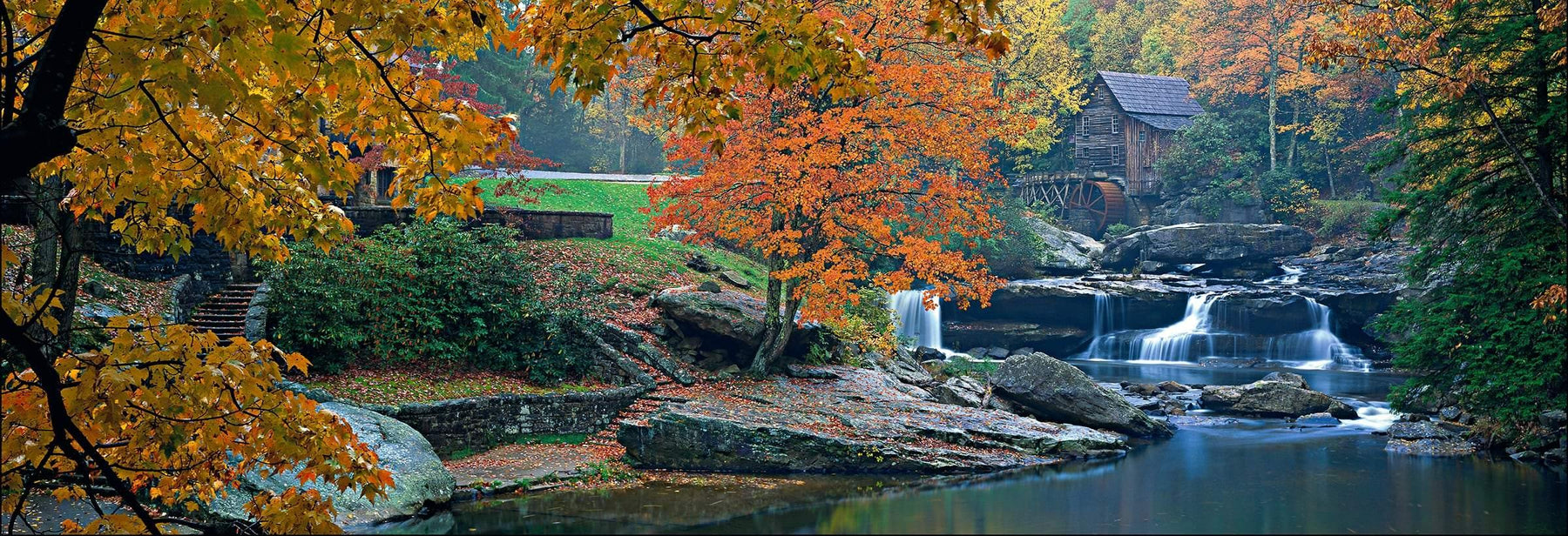 Autumn branches hanging over the rivers edge in front of  Glade Creek Grist Mill in the Appalachian Mountains