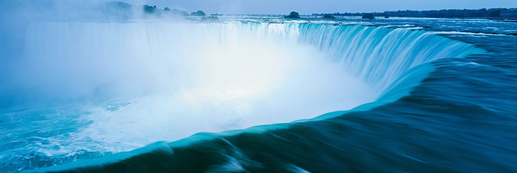 Giant turquoise waterfalls forming a horseshoes shape at Niagara Falls New York