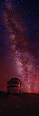 Observatory on the mountainside of Mauna Kea Hawaii below a sky filled with stars and the Milky Way