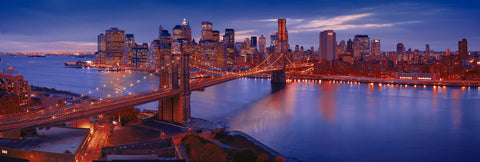 Rooftop view of New York and the Brooklyn Bridge lit up at twilight reflecting on the East River
