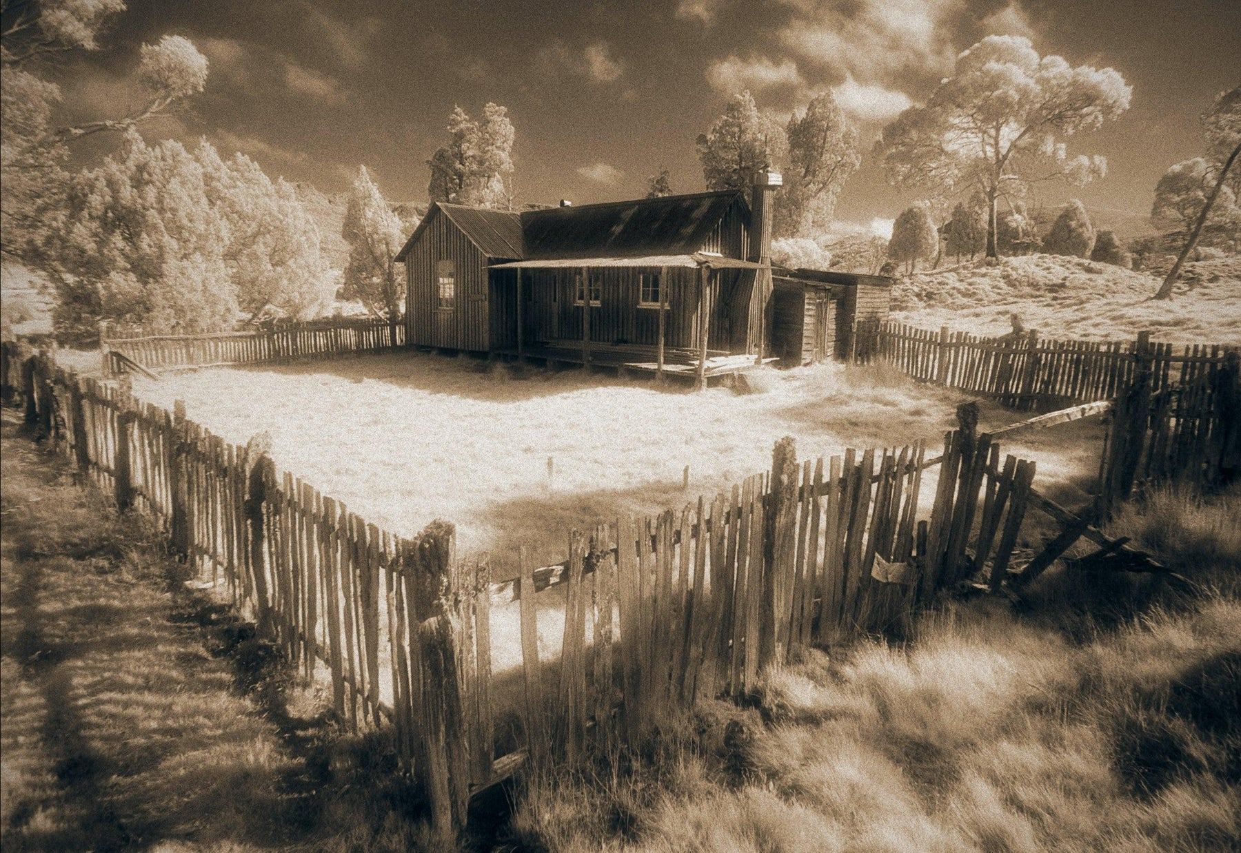Old house in the valley of Cradle Mountain Australia surrounded by trees and a picket fence in a sepia color tone