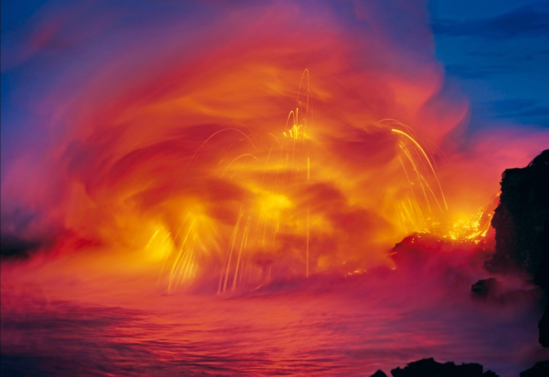 Blurred explosion of fire and lava hitting the ocean water on the shoreline of Kilauea Hawaii
