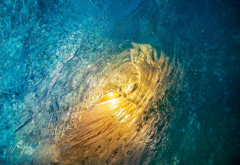 Looking out at the  sun from inside a blue crashing wave in Maui Hawaii