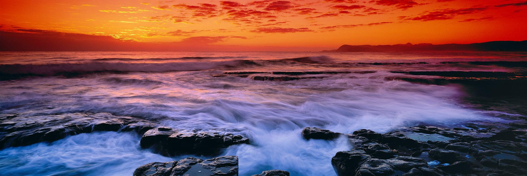 Waves crashing during sunrise off a rocky beach in Tasmania at sunset