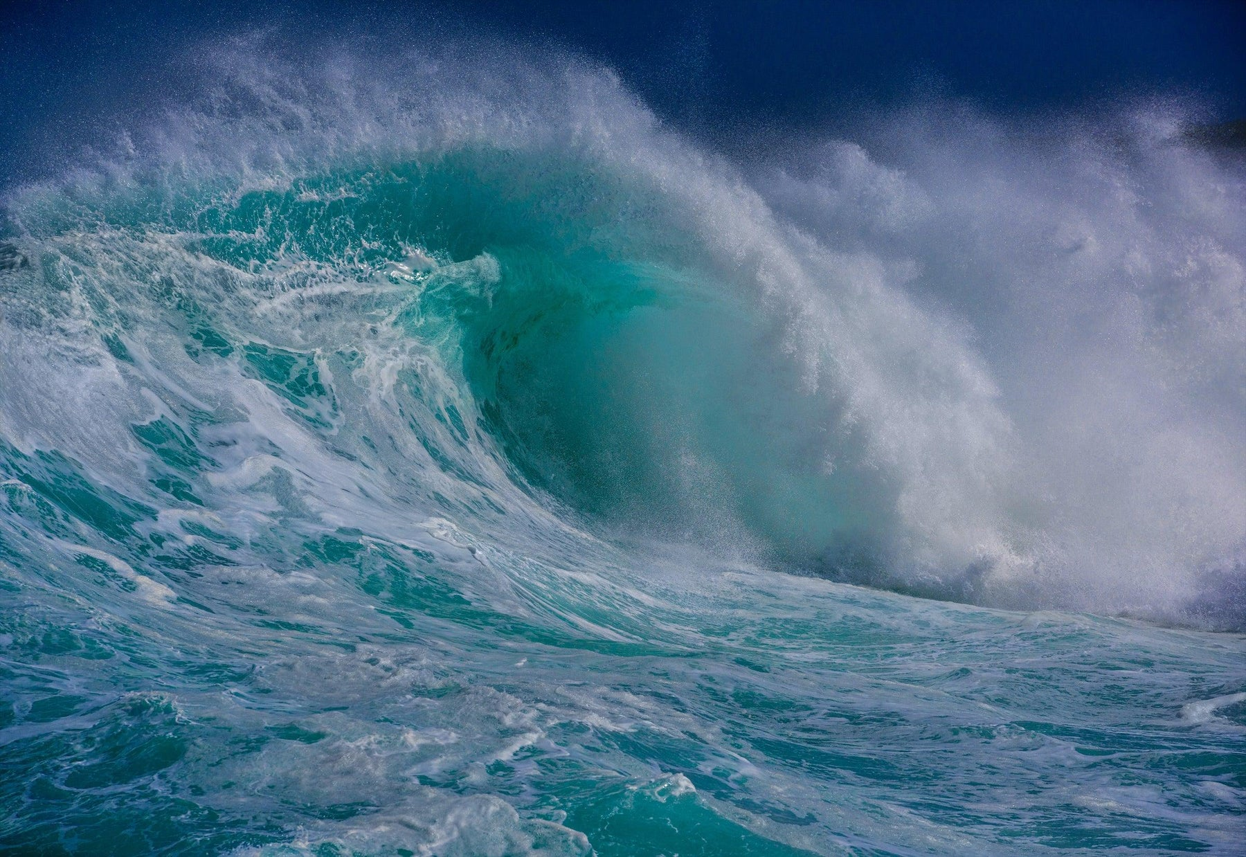 Large white and turquoise wave crashing into the ocean in Maui Hawaii