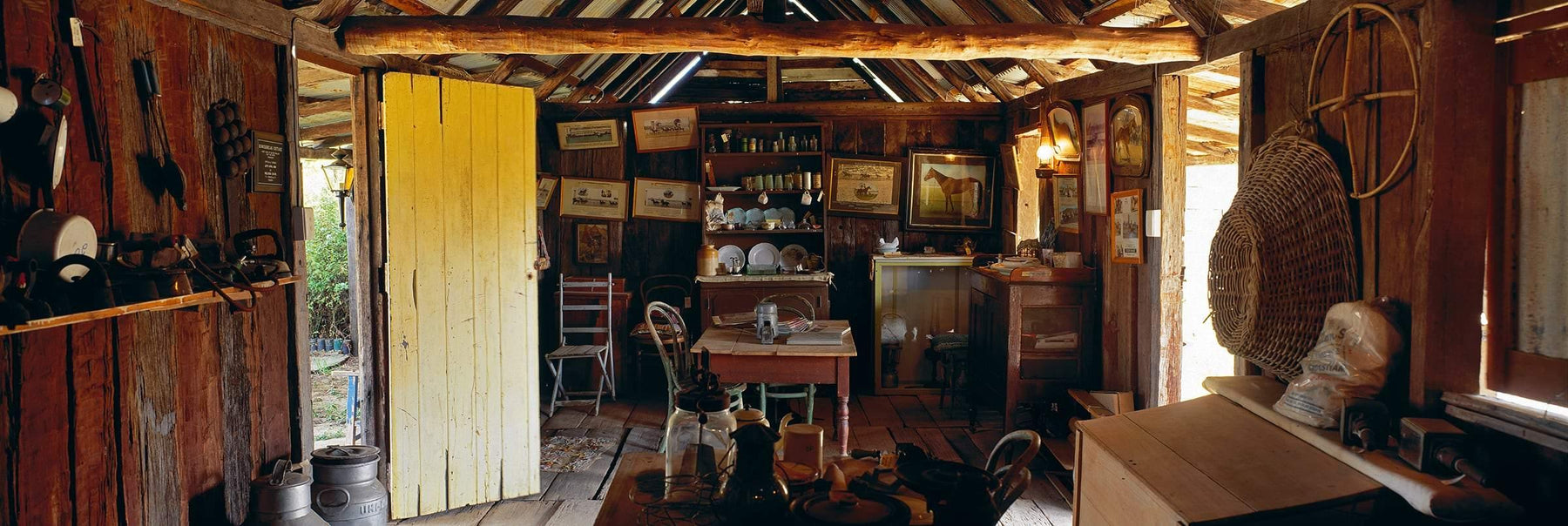 Interior of an old wooden shack filled with framed pictures table and chairs dishes and other miscellaneous items