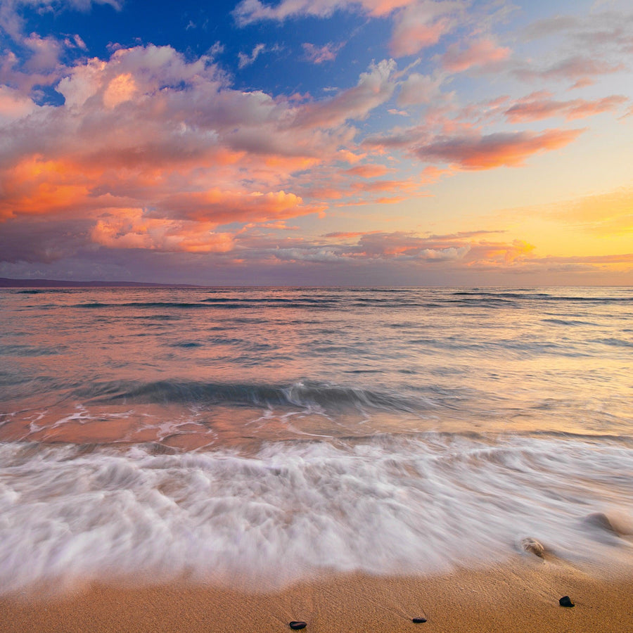 Waves washing along a sandy beach with rocks under a cloudy sky at sunset