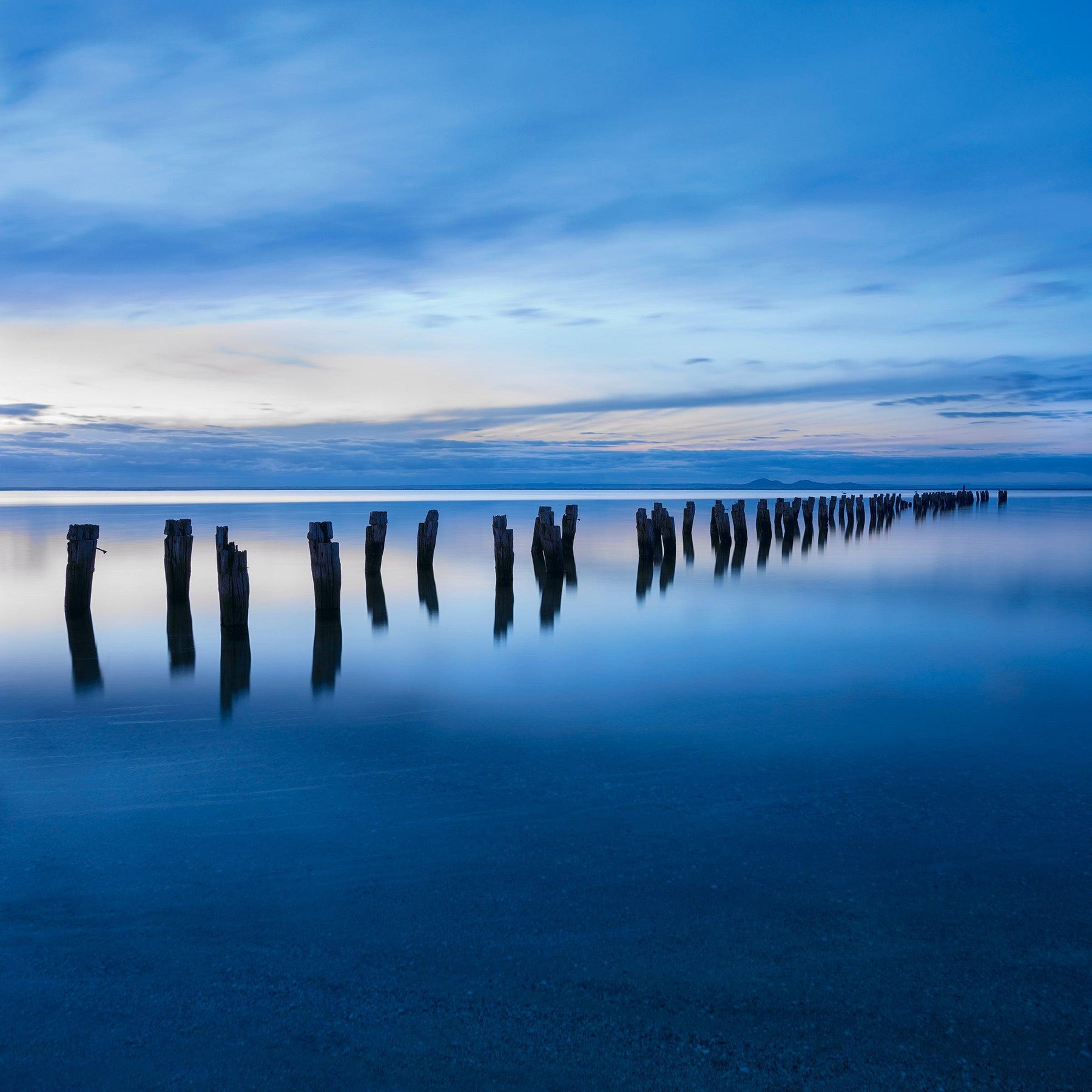 Remains of an old wooden jetty leading into a bay in Victoria Australia at sunrise