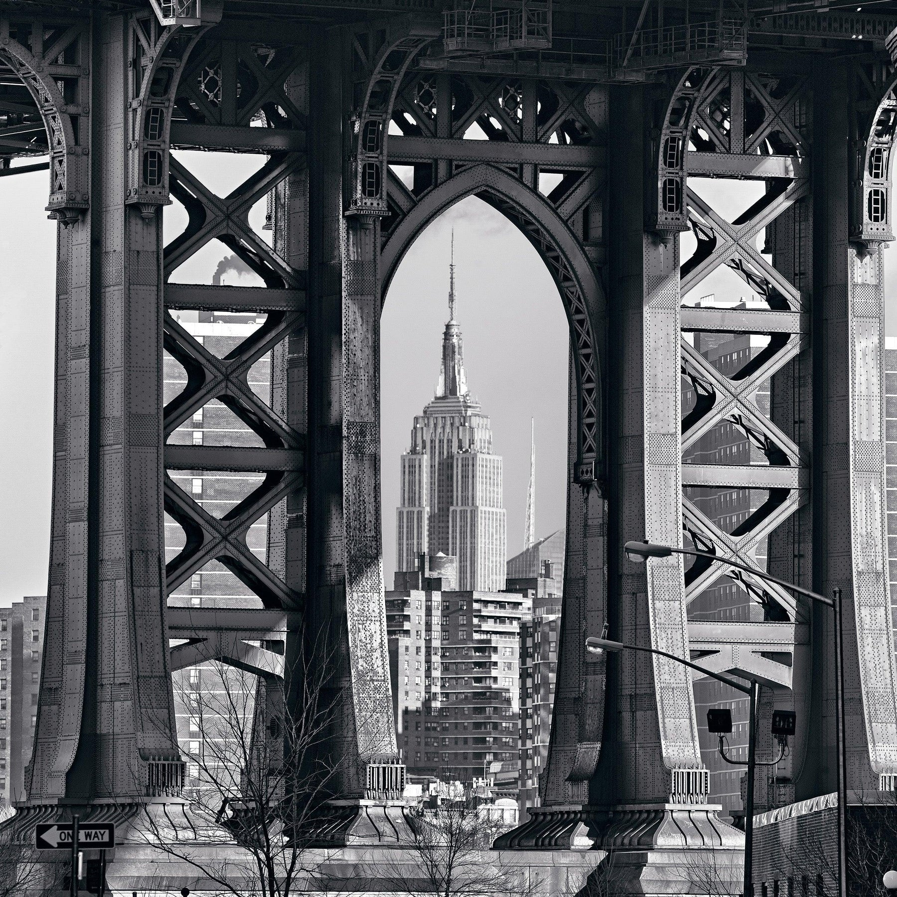 Black and white of the Empire State Building framed within the arches under the Manhattan Bridge New York