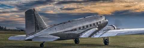 Side view of a DC-3 airplane taking off from a grass runway in Portland Oregon