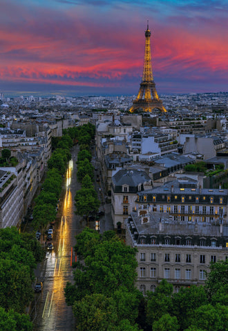 Rooftop view of the streets of Paris France and the Eiffel Tower lit up at sunset