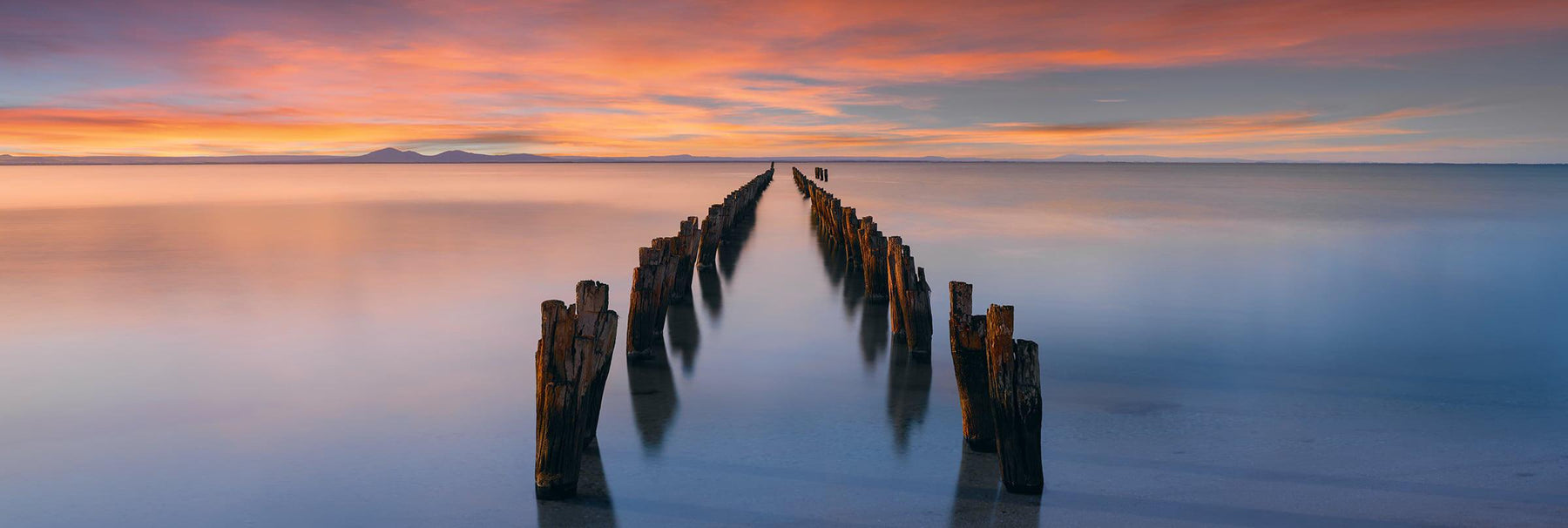 Remains of an old wooden jetty leading into a bay in Victoria Australia at sunset