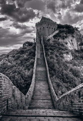 Black and white stone path of The Great Wall of China leading up an mountain to one of its towers