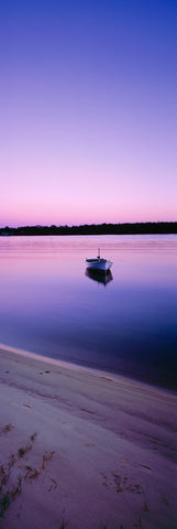 Dinghy floating off the banks of the Noosa River at sunrise with the purple sky reflecting off the water