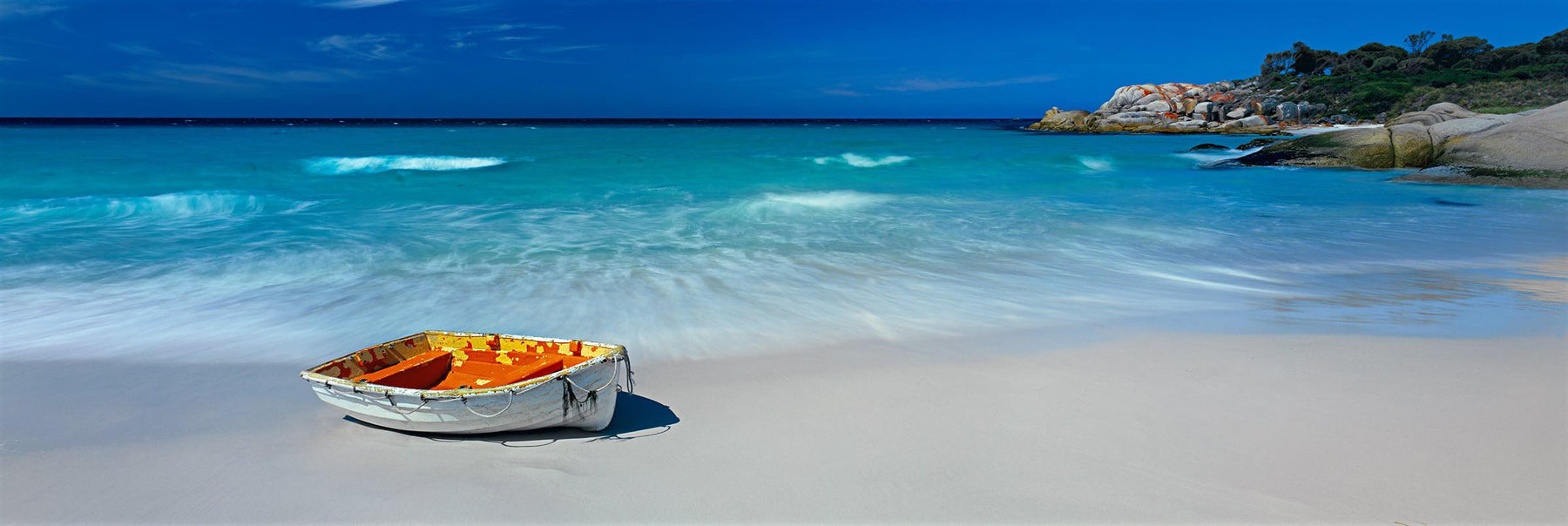 White and orange wooden row boat on the sandy beach of Wineglass Bay Australia