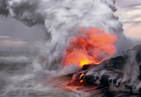 Fire and lava hitting the ocean water creating a giant cloud of steam and smoke on the shoreline of Kilauea Hawaii