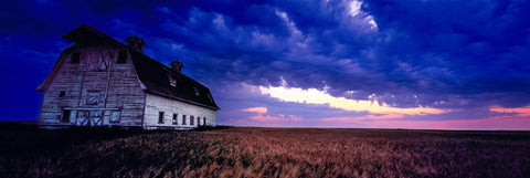 Weathered old white barn in the middle of a wheat field in North Dakota as a storm rolls in