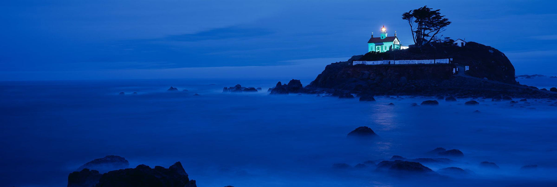 Battery Point Lighthouse in Crescent City California lit up before sunrise