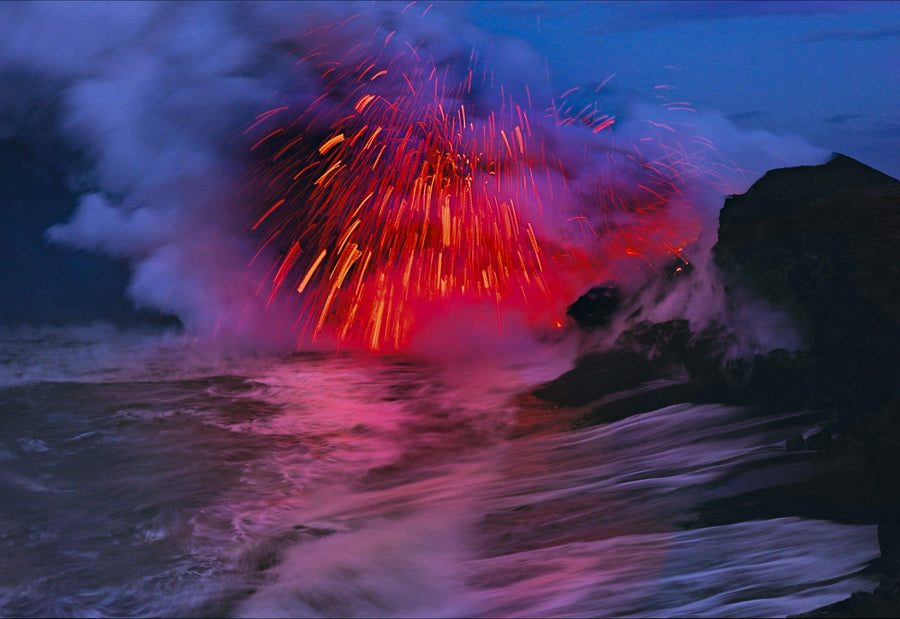 Explosion of fire and lava hitting the ocean water creating a cloud of smoke on the shoreline of Kilauea Hawaii